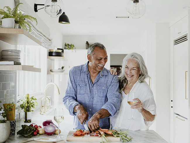 retired couple in the kitchen, cooking and enjoying themselves.