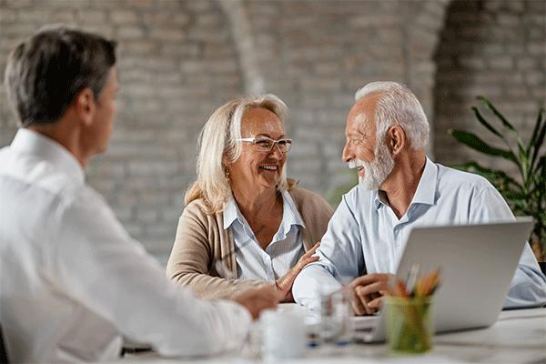 Senior couple taking to financial advisor, reasons to buy priority gold.
