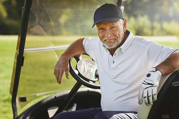 senior man smiling on his golf cart.
